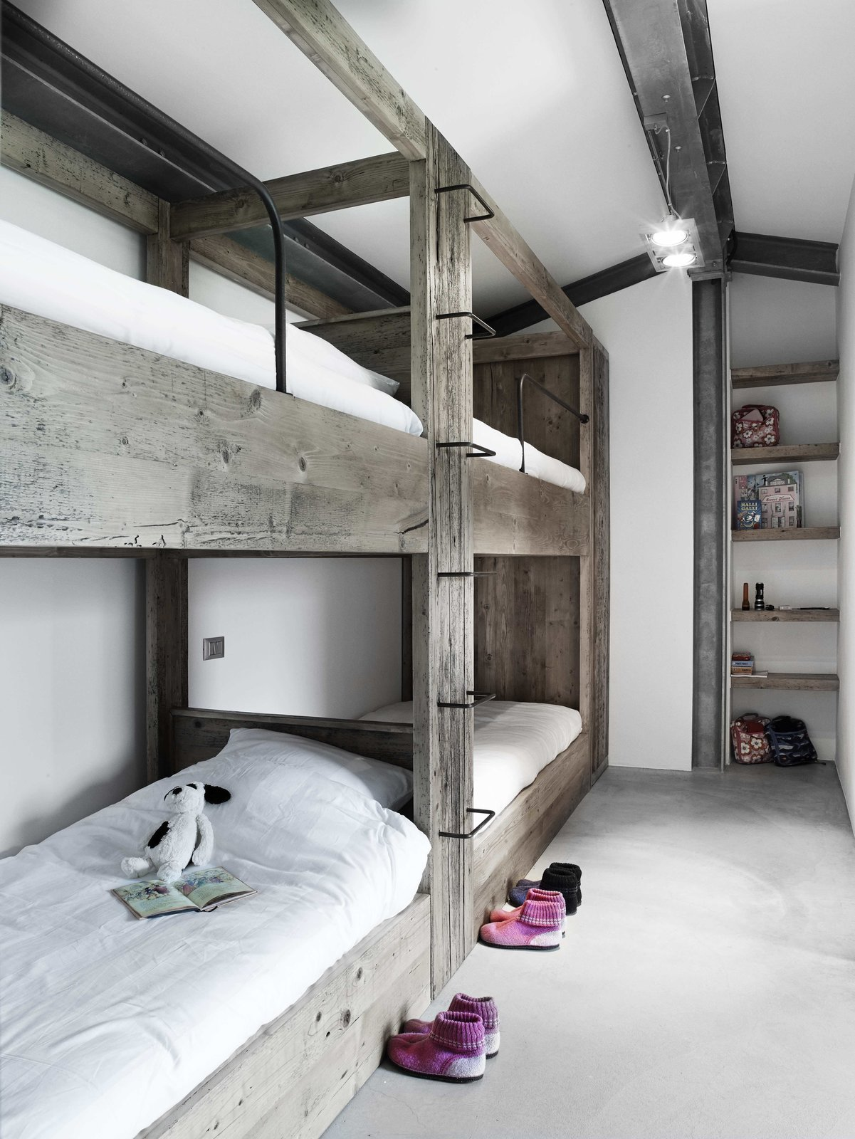 Tagged: Kids, Bed, Concrete, Bedroom, Pre-Teen, Neutral, Shelves, and Bunks.  Best Kids Photos from Stay in a Modern, Industrial Home That's Hidden Inside a Traditional Tuscan Villa