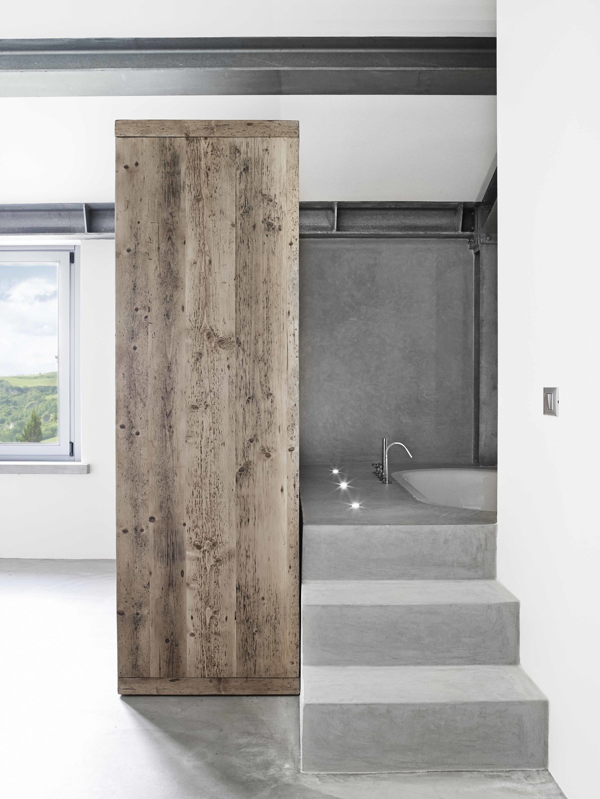 Bath Room, Undermount Tub, Soaking Tub, Concrete Floor, and Accent Lighting  Photo 10 of 11 in Stay in a Modern, Industrial Home That's Hidden Inside a Traditional Tuscan Villa