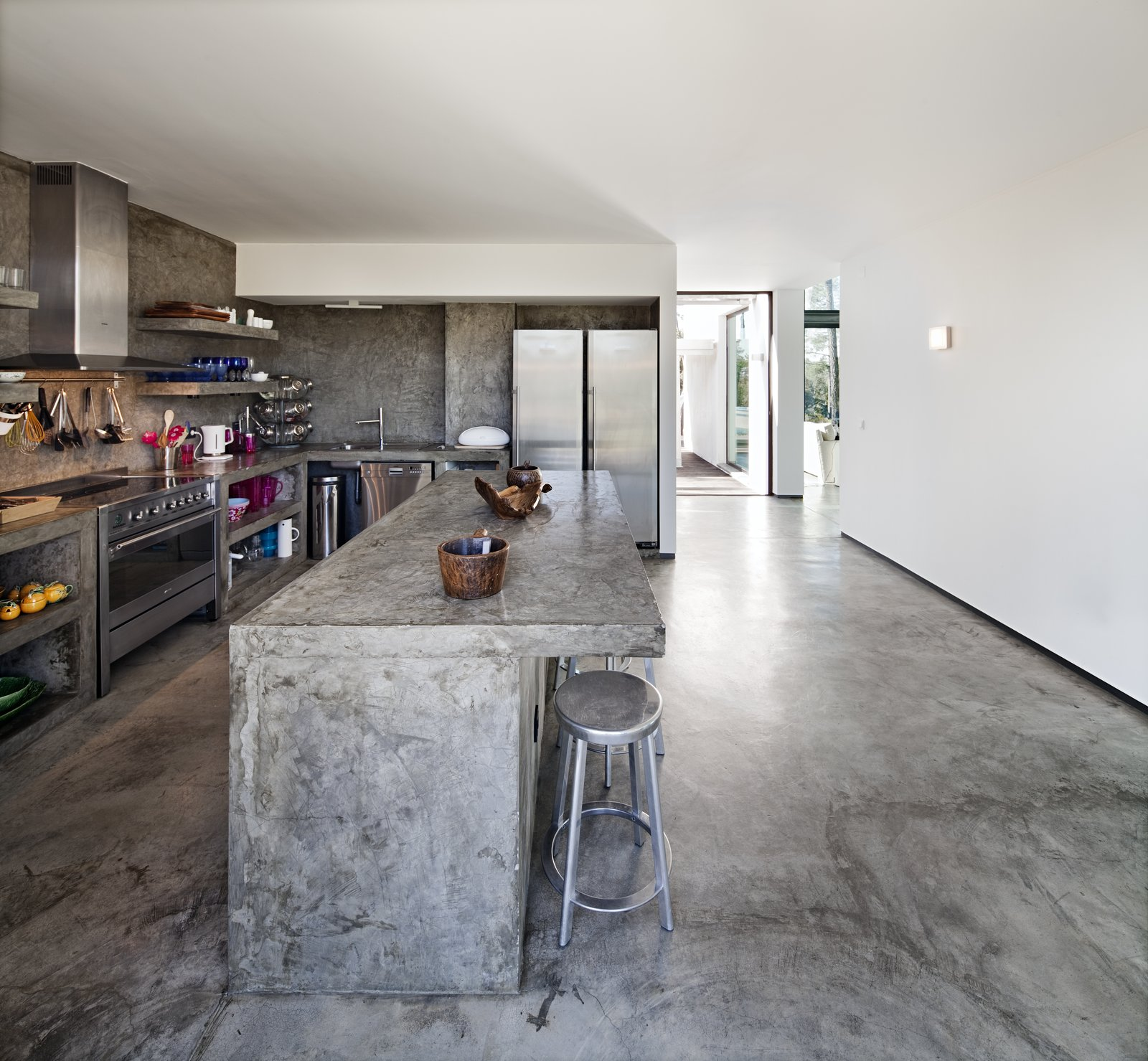 Kitchen, Concrete, Dishwasher, Range Hood, Wall Oven, Refrigerator, Drop In, Concrete, Open, Wall, Cooktops, Ceiling, and Concrete  Best Kitchen Drop In Cooktops Wall Photos from Escape to a Light-Filled, Beach-Meets-Forest Retreat in Portugal