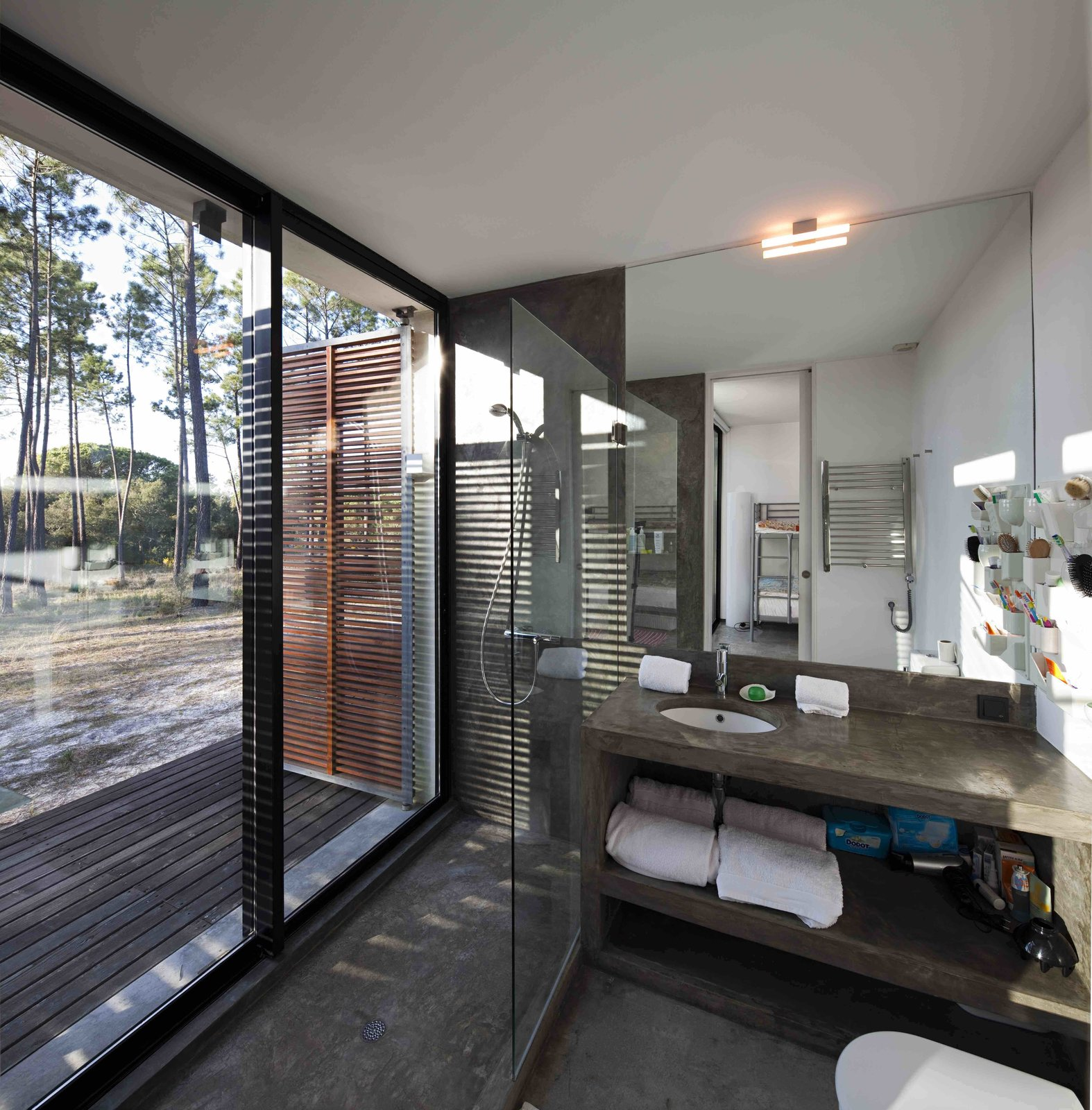 Bath Room, Concrete Counter, Concrete Floor, Open Shower, Wall Lighting, and Undermount Sink  Photo 7 of 15 in Escape to a Light-Filled, Beach-Meets-Forest Retreat in Portugal