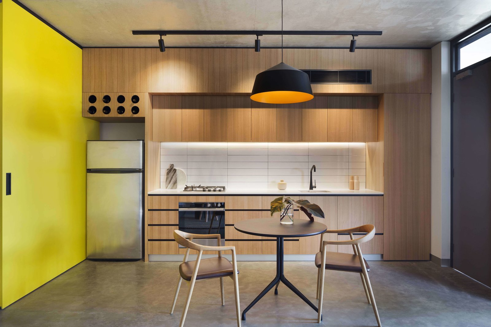 Kitchen, Wood Cabinet, Ceramic Tile Backsplashe, Pendant Lighting, Refrigerator, Wall Oven, Concrete Floor, Drop In Sink, and Cooktops  Photo 11 of 14 in What Looks Like a Single Dwelling in Melbourne Actually Holds Six Walk-Up Apartments