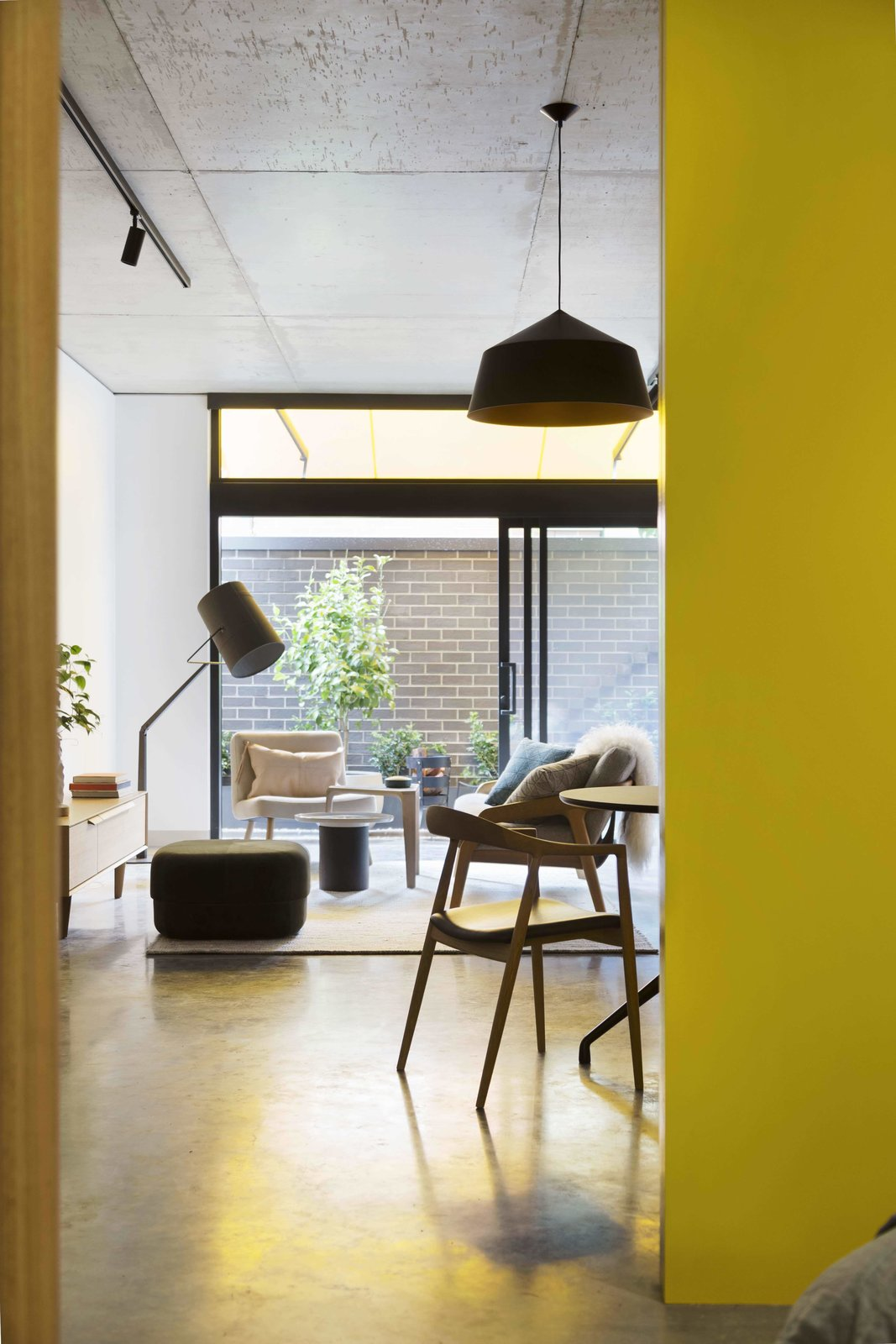 Living Room, Chair, Ottomans, Table, Lamps, Pendant Lighting, Concrete Floor, and Floor Lighting  Photo 13 of 14 in What Looks Like a Single Dwelling in Melbourne Actually Holds Six Walk-Up Apartments