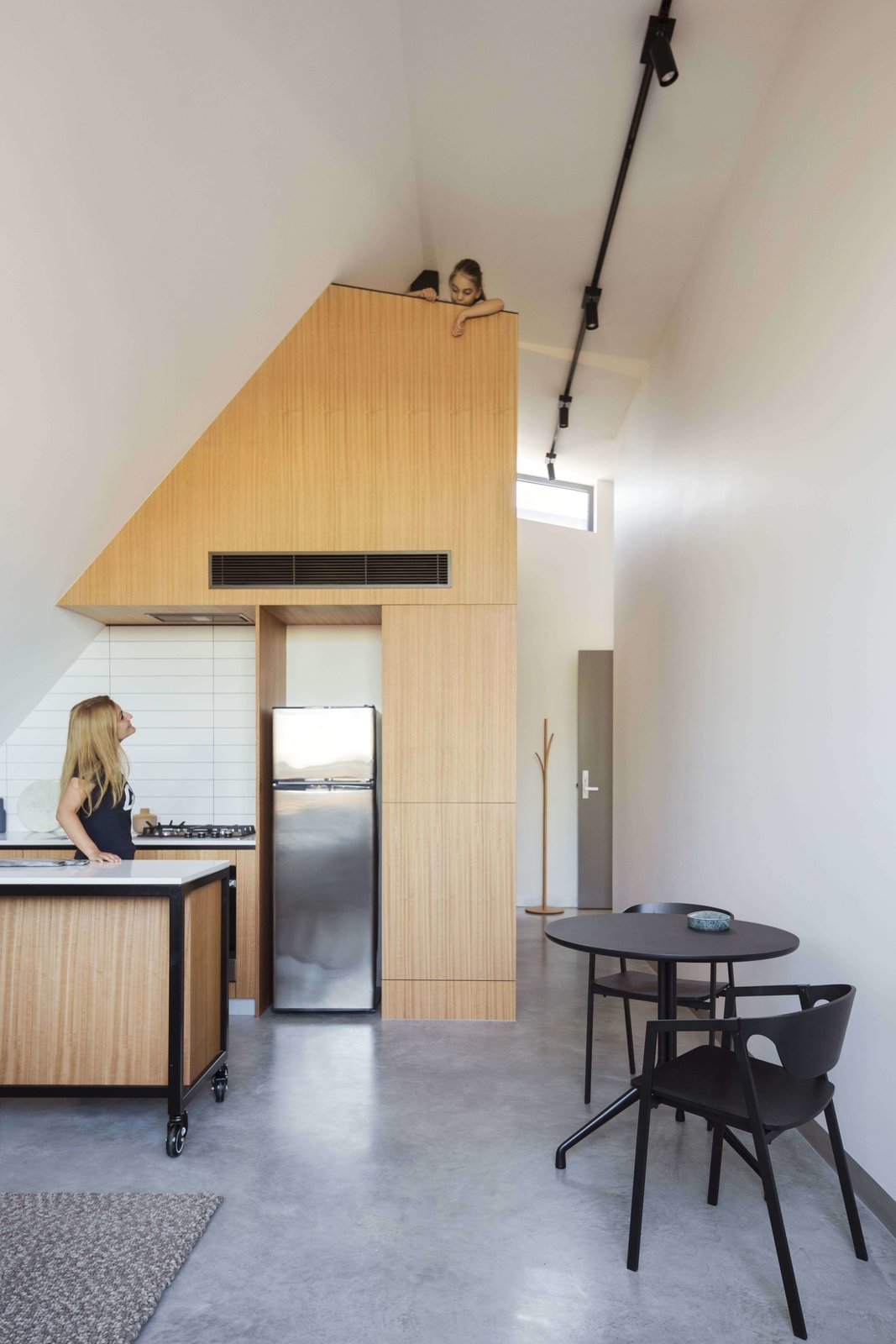 Kitchen, Wood Cabinet, Concrete Floor, Refrigerator, Ceiling Lighting, and Cooktops  Photo 14 of 14 in What Looks Like a Single Dwelling in Melbourne Actually Holds Six Walk-Up Apartments