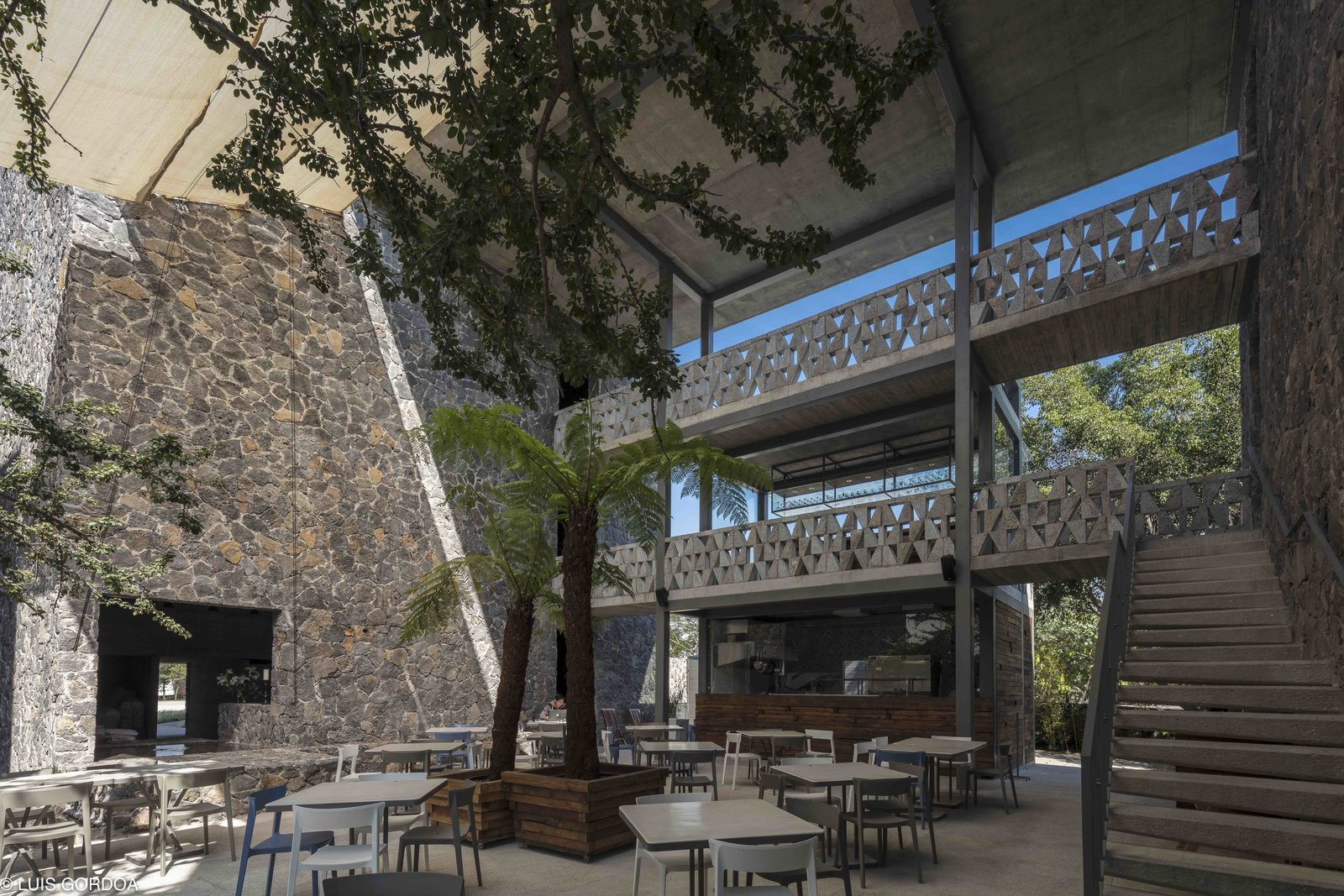 Mexican architect Alfredo Cano of T3arc completed Hotel Huayacan, a 27,986-square-foot, 40-room hotel with robust stone facades. Tagged: Outdoor, Trees, Concrete Patio, Porch, Deck, and Large Patio, Porch, Deck.  Photo 1 of 12 in A New Hotel in Morelos Combines Local Mexican Elements With Brutalist Architecture