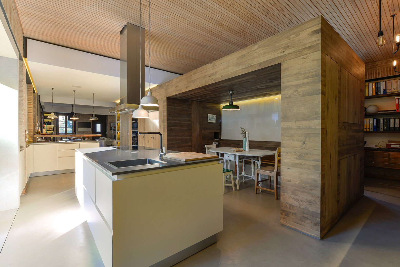 Kitchen, Metal Counter, White Cabinet, Concrete Floor, Pendant Lighting, Cooktops, Drop In Sink, and Range Hood  Photo 10 of 16 in An Architect Renovates His 1920s Home in Portugal, While Preserving the Exterior Shell