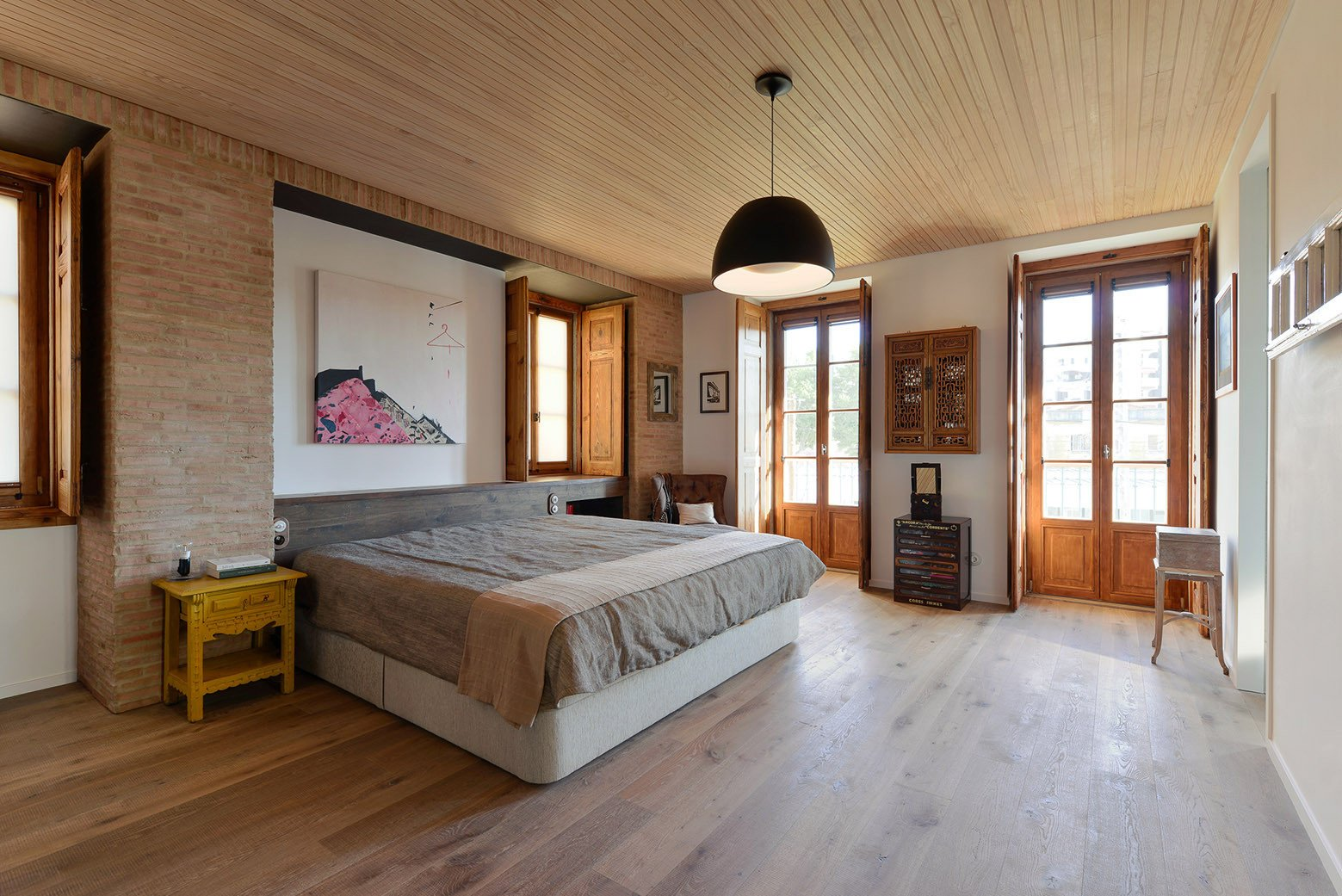 Bedroom, Pendant Lighting, Bed, Chair, Night Stands, and Light Hardwood Floor  Best Photos from An Architect Renovates His 1920s Home in Portugal, While Preserving the Exterior Shell
