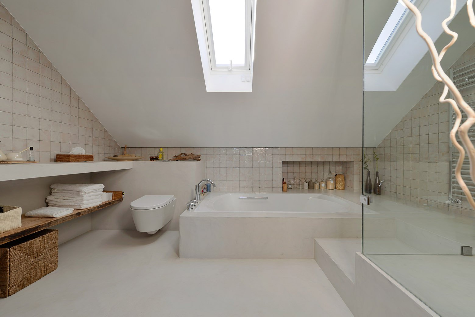Bath Room, Concrete Floor, Drop In Tub, Ceramic Tile Wall, and One Piece Toilet  Best Photos from An Architect Renovates His 1920s Home in Portugal, While Preserving the Exterior Shell