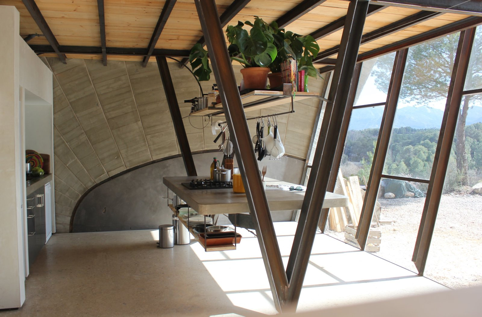 Kitchen, Concrete Counter, and Range  Super Cool Kitchen Islands by Erika Heet from Stay in a Domed, Glass-Front Vacation Home in a Spanish Forest