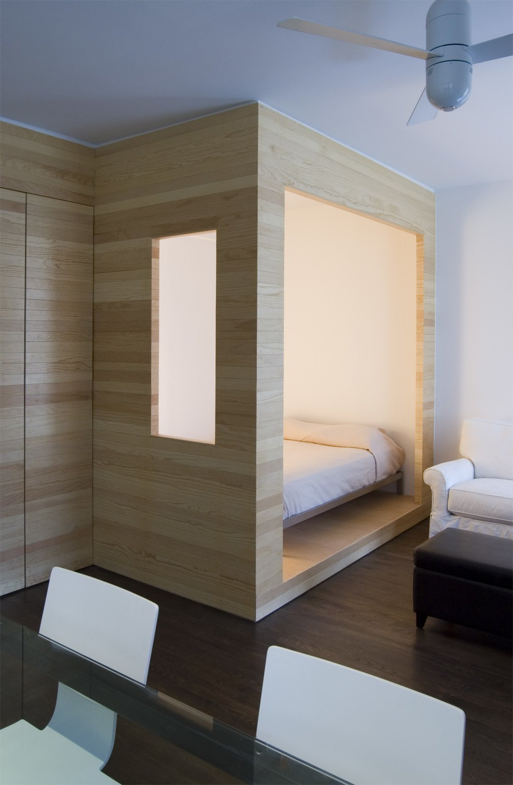 Framework Architecture created a partially enclosed sleeping nook in this tiny Brooklyn studio apartment, which snuggly fits a full-sized bed. Tagged: Bedroom, Bed, Accent Lighting, Dark Hardwood Floor, and Chair.  Photo 4 of 11 in 11 Hidden Beds in Small Homes