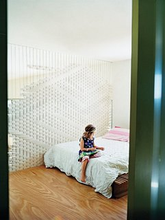 At Cat Macleod and Michael Bellemo's split-level home in Melbourne, a loft bedroom features a clever divider that Macleod created out of woven engineering felt.