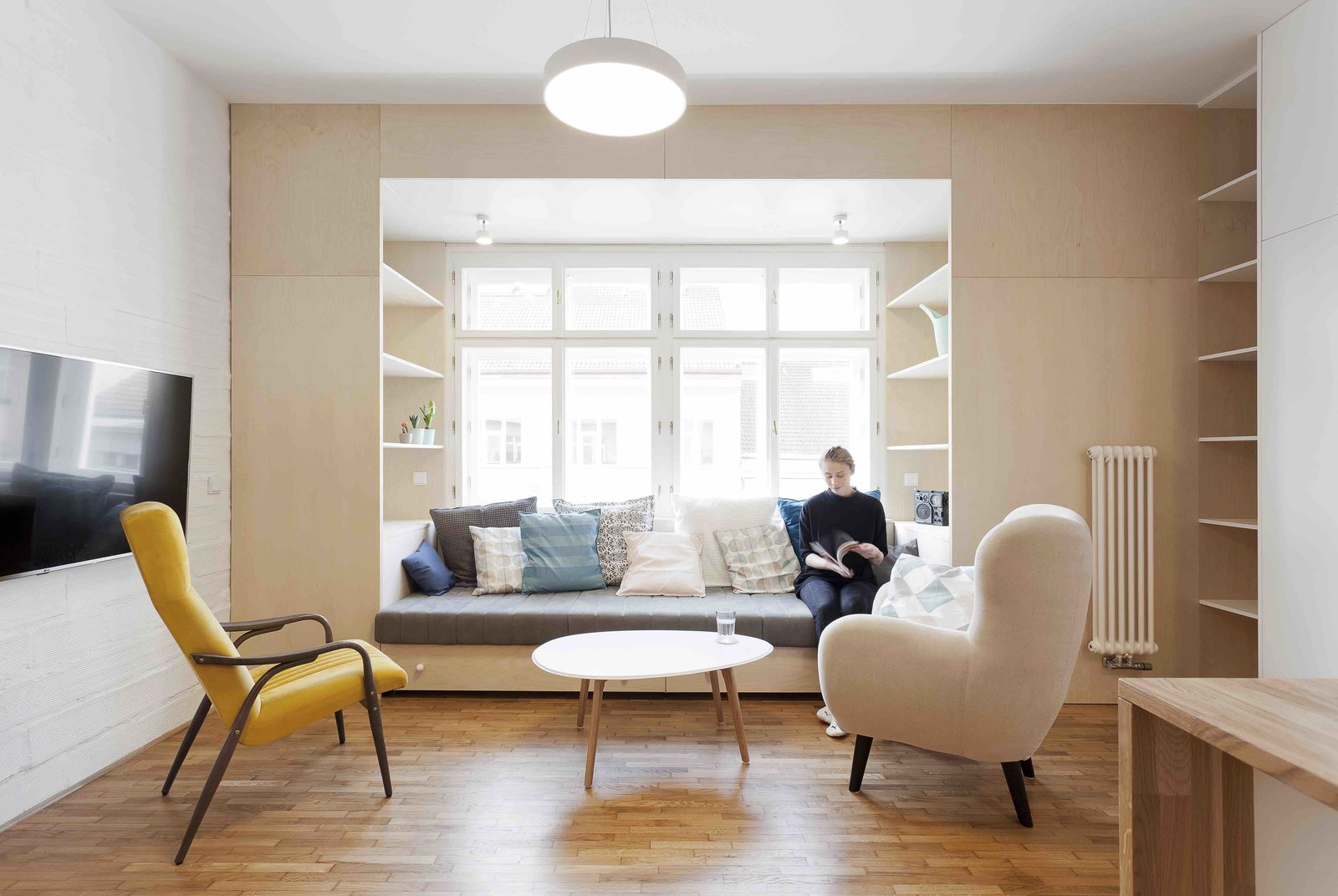 Tagged: Living Room, Chair, Sofa, Bookcase, Coffee Tables, Medium Hardwood Floor, Pendant Lighting, and Shelves.  Best Photos from A Family Apartment in Prague That's Filled With Clever Storage Solutions and Built-In Nooks
