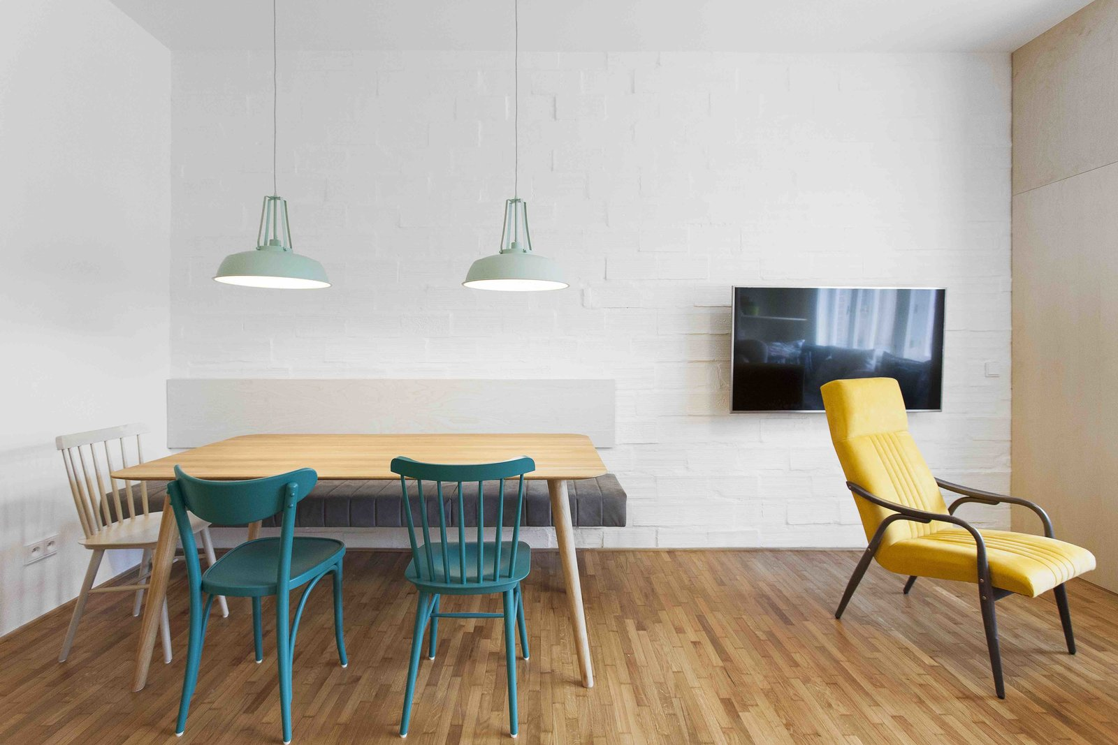 Dining Room, Table, Pendant Lighting, Medium Hardwood Floor, Chair, and Bench  Photo 2 of 13 in A Family Apartment in Prague That's Filled With Clever Storage Solutions and Built-In Nooks