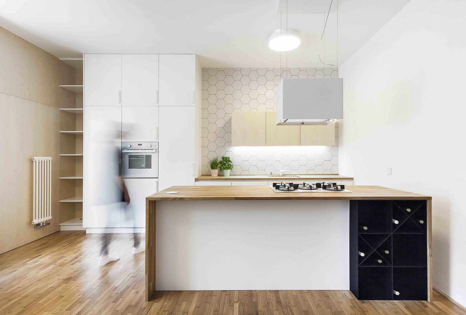 Kitchen, White Cabinet, Medium Hardwood Floor, Wood Counter, Range, Ceiling Lighting, Range Hood, Wall Oven, Ceramic Tile Backsplashe, and Undermount Sink  Photo 4 of 13 in A Family Apartment in Prague That's Filled With Clever Storage Solutions and Built-In Nooks