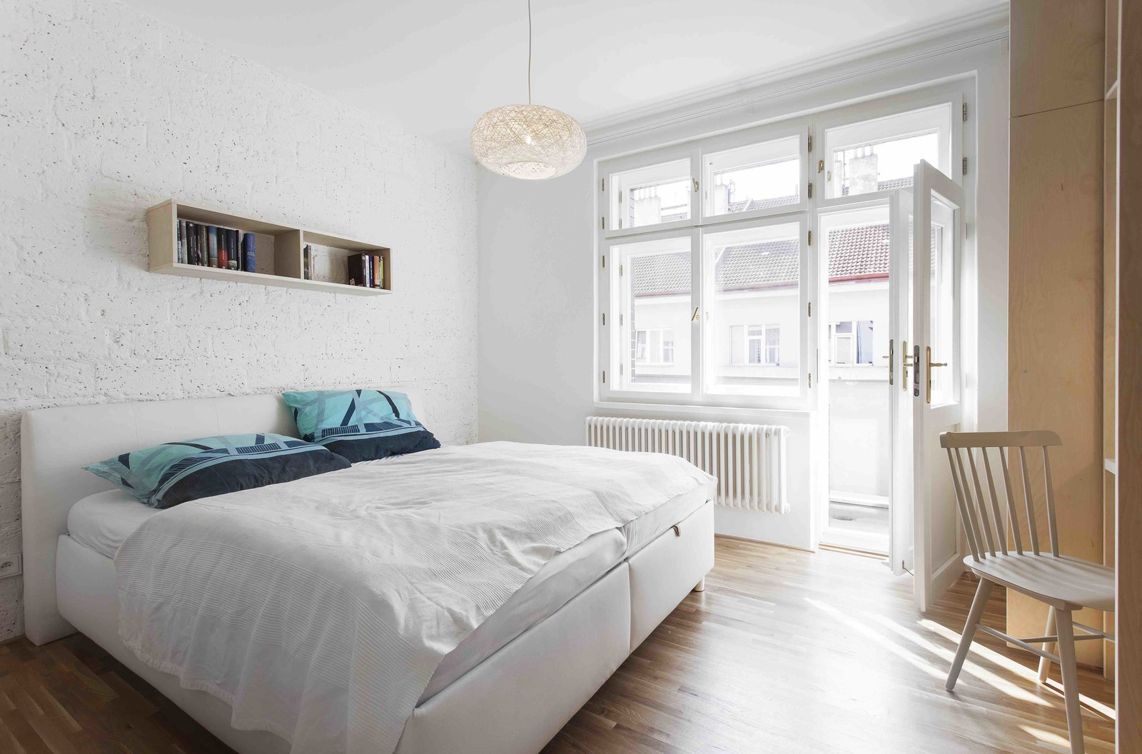 Bedroom, Bookcase, Medium Hardwood Floor, Pendant Lighting, Bed, and Chair  Photo 6 of 13 in A Family Apartment in Prague That's Filled With Clever Storage Solutions and Built-In Nooks