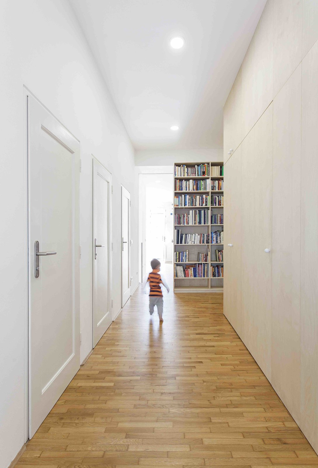 Hallway and Medium Hardwood Floor  Photo 9 of 13 in A Family Apartment in Prague That's Filled With Clever Storage Solutions and Built-In Nooks
