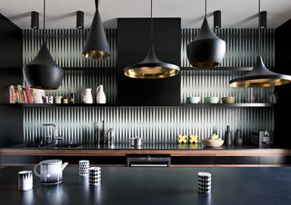 This dark and bold kitchen features Beat Pendants by Tom Dixon and a black-and-white tile backsplash by Popham Design.