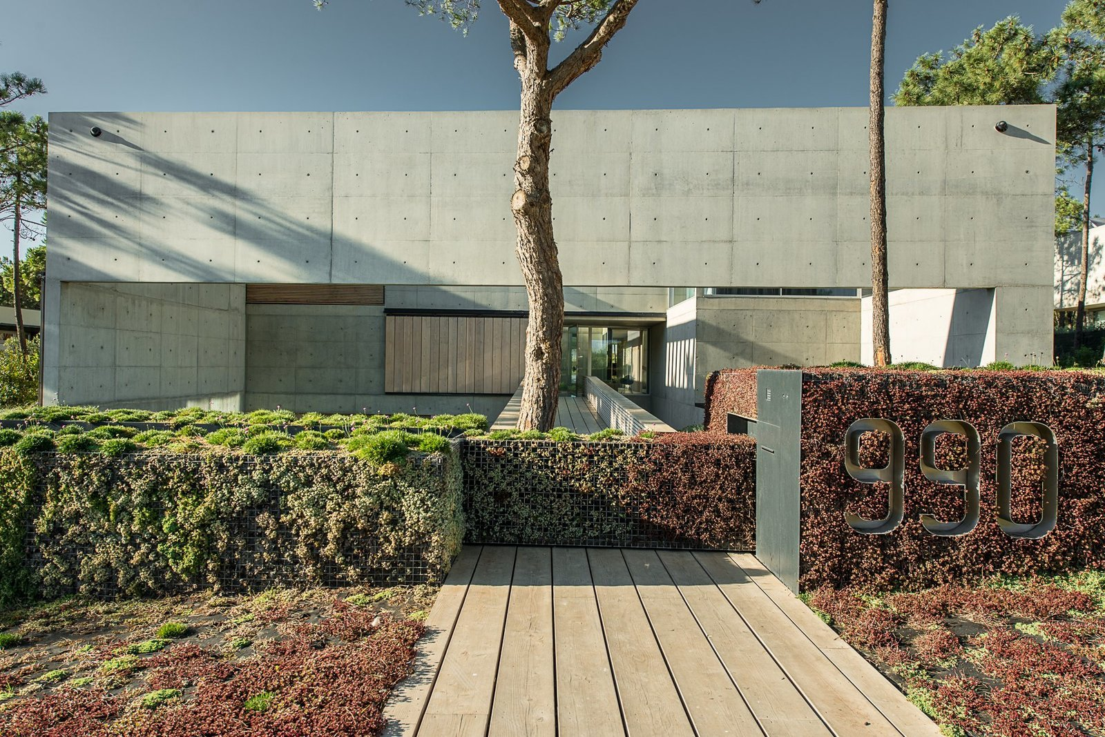 The Wall House entrance with garden walls and large metal street numbers.