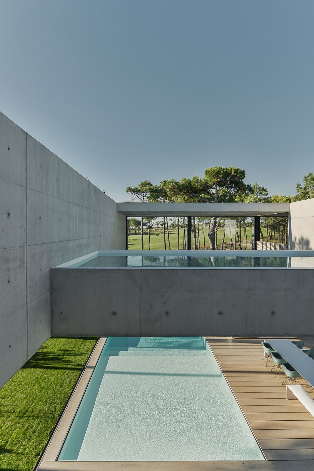 The Wall House view of second level glass bottom pool above ground level pool.