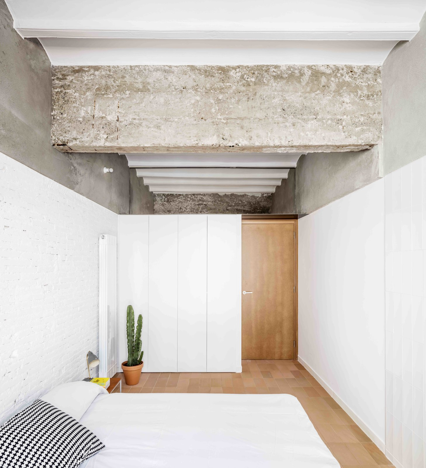 Bedroom, Bed, Porcelain Tile, Table, Wall, Storage, and Lamps  Best Bedroom Bed Porcelain Tile Photos from This Double-Height Apartment in   Barcelona Features Historic Details and a Floating Staircase