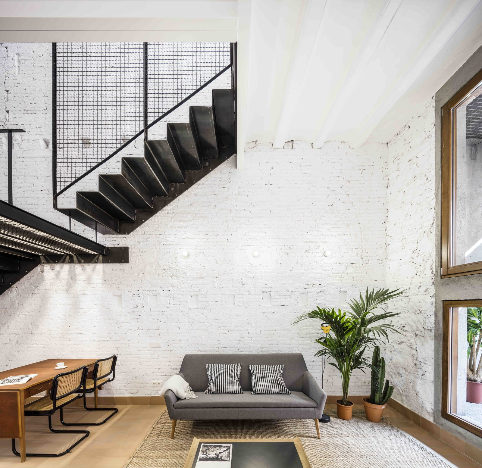 Living Room, Table, Chair, Sofa, Coffee Tables, and Wall Lighting  Photo 13 of 13 in This Double-Height Apartment in   Barcelona Features Historic Details and a Floating Staircase
