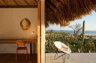 Architect Federico Rivera Rio updated traditional beach huts in Oaxaca with palapa roofs, transforming them into stylish, minimalist bungalow hotel rooms with stucco walls, wooden floors, and polished concrete bathrooms.