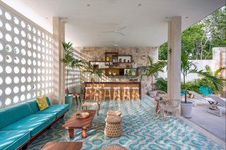 Inspired by midcentury architecture in Miami, this hotel located within a yoga retreat community center known as Holistika Tulum is a retro jungle oasis with cool custom-made floor tiles, rattan chairs, and a calming aquamarine color scheme.