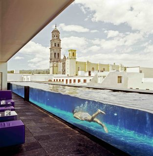 Modern furniture harmonizes with the old stone columns and walls of a former 19th-century water purification factory in this boutique hotel in Puebla. Archeological finds such as bottles and glass fragments from the old factory were incorporated into the interior design.