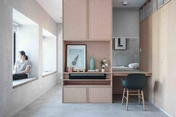 """10 Small Apartments by a Hong Kong Design Studio That Are Less Than 1,000 Square Feet - Photo 3 of 10 - Inspired by modern Japanese minimalism, the walls of this two-bedroom apartment were demolished, transforming the space into a studio with an """"Engawa""""—a space  between the indoor and outdoor areas that's often found in traditional Japanese architecture and helps maximize light penetration into the interiors. Kevin's home also has a working desk that's fitted with a retractable curtain for privacy."""