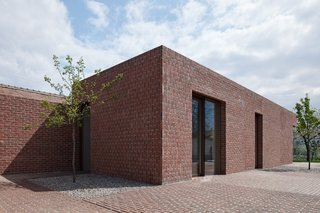 10 Modern Structures That Use Brick in Interesting Ways - Photo 9 of 10 - Constructed almost entirely of red brick, this clean-lined, L-shaped row house in the Czech Republic juxtaposes walls of vertically laid bricks with walls of horizontally laid bricks. The pavements along the gardens surrounding the house are laid with the same type of bricks. The overall effect is a home that looks as if it grew from a ground of bricks.