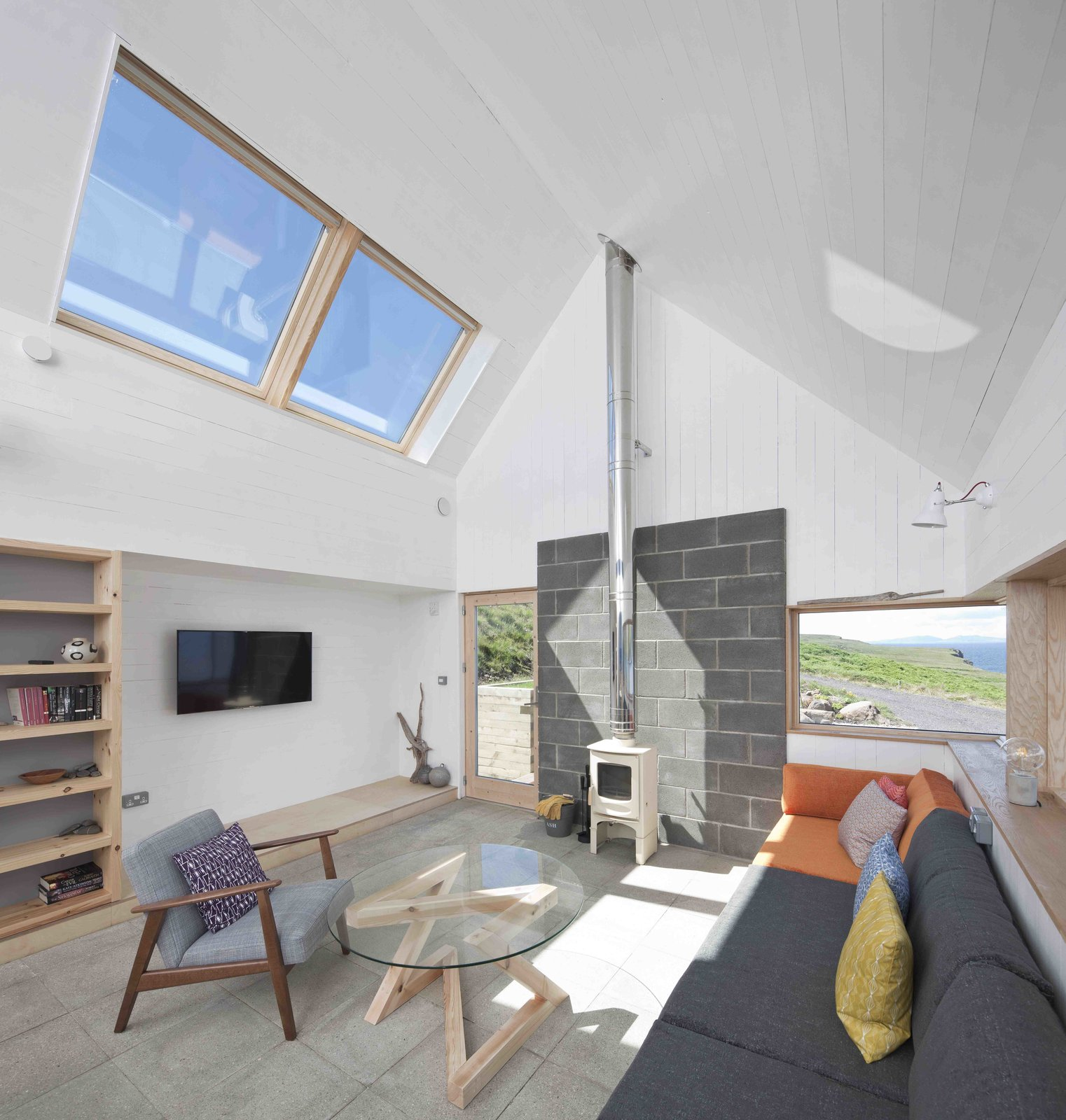 Living Room, Sofa, Coffee Tables, Shelves, Chair, Concrete Floor, Bookcase, Wall Lighting, and Wood Burning Fireplace  Photo 2 of 11 in Stay in a Modern Tin Cottage on Scotland's Isle of Skye