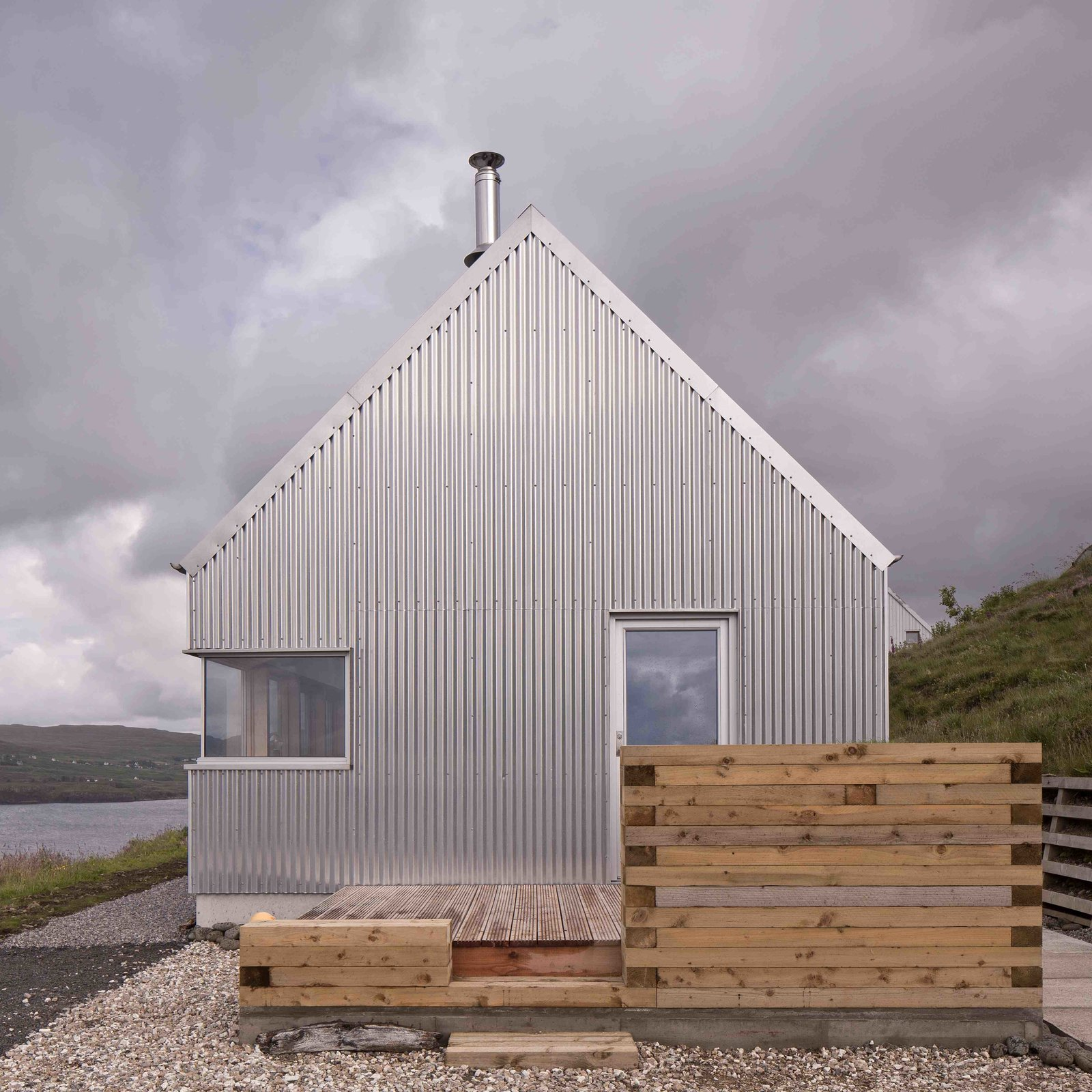 Outdoor, Side Yard, Wood Patio, Porch, Deck, Grass, Small Patio, Porch, Deck, Horizontal Fences, Wall, and Wood Fences, Wall  Photo 3 of 11 in Stay in a Modern Tin Cottage on Scotland's Isle of Skye