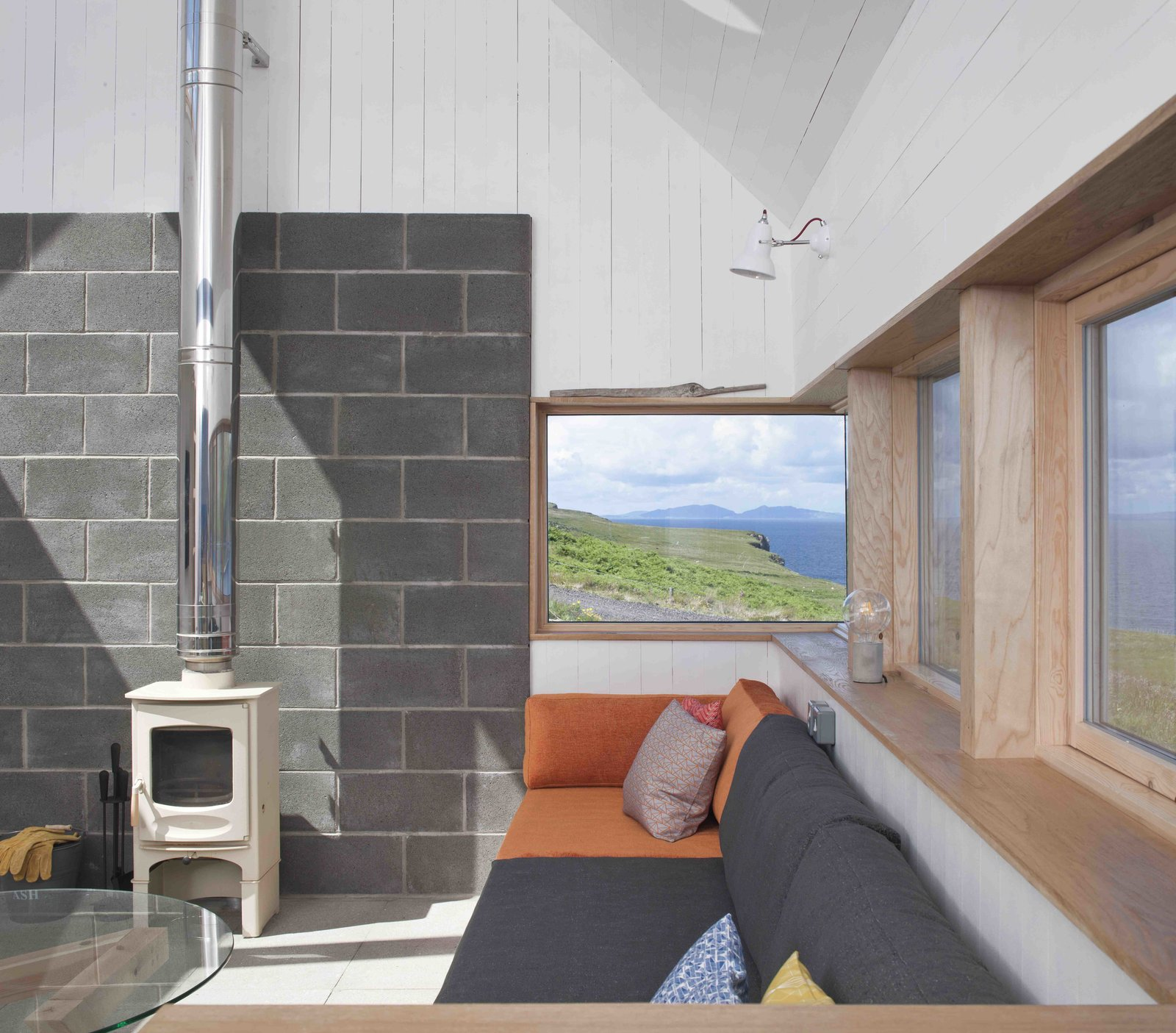 Living Room, Coffee Tables, Wall Lighting, Sofa, Wood Burning Fireplace, and Concrete Floor  Photo 9 of 11 in Stay in a Modern Tin Cottage on Scotland's Isle of Skye