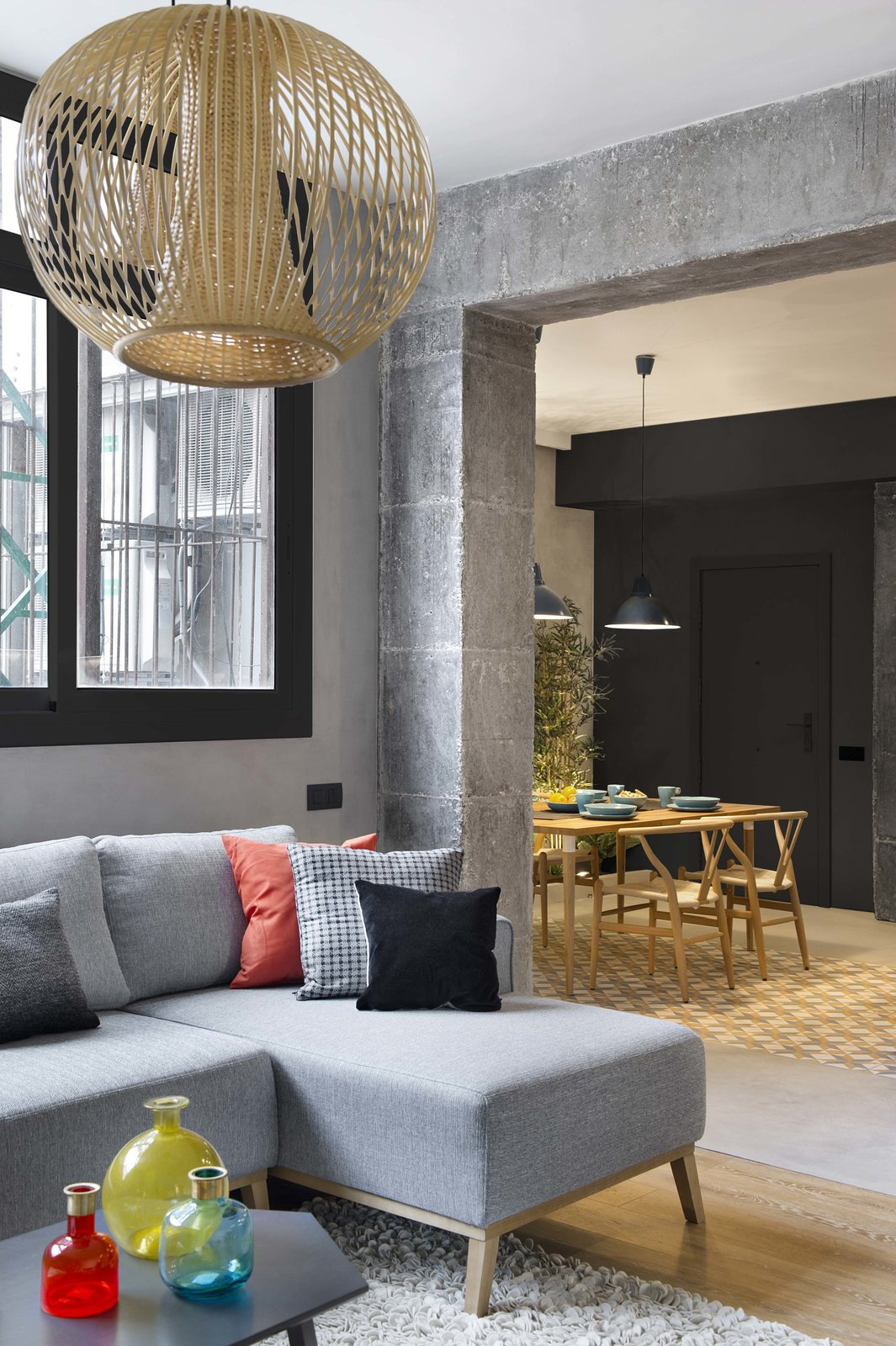 Living Room, Sofa, Pendant Lighting, and Medium Hardwood Floor  Photo 6 of 11 in In This Compact Barcelona Apartment, Space Is Maximized With Smart Material Choices