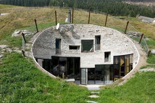 8 Subterranean Homes That Are Out of This World - Photo 1 of 8 - Looking like a burrow on the side of a mountain, Villa Vals—a Swiss vacation rental available through Boutique Homes—was designed by Architects Bjarne Mastenbroek of SeARCH and Christian Müller of CMA. The entrance to the property is through a nearby wooden barn, which has a concealed underground tunnel that runs through the mountain into the villa's subterranean core.