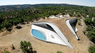 Embedded into the top of a hill, Villa Ypsilon in the Greek seaside village of Messenia has a Y-shaped, earth-covered roof promenade that looks as if it's an extension of the terrain.