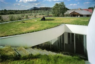 "8 Subterranean Homes That Are Out of This World - Photo 7 of 8 - OUTrail House by Polish architectural practice KWK PROMES has a basement level that was ""carved out"" of a piece of the grass-covered site. The roof has been turned into a green atrium that blends in with its grassy surroundings."