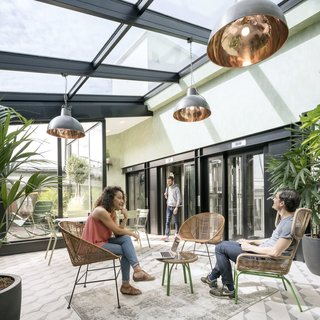 On the sixth floor of Airbnb's Paris office is a bright, plant-filled solarium where staff can relax and socialize. Designed by Airbnb in collaboration with STUDIOS Architecture, the space has all the relaxed breeziness of a Parisian attic loft.