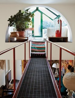 The late Italian designer-architect Gae Aulenti's home in Milan has a catwalk that begins in the living room and leads up to a solarium sitting area.