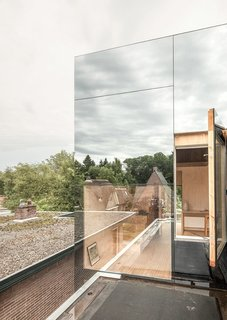 "With an extension clad in mirrored glass that reflects the silhouettes of the existing brick house, ""Mirror Mirror"" is a home that shields its residents from view during the day, but exposes the extension's interiors at night."