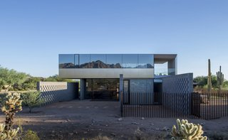 Szu-Ping Patricia Chen Suchart and Thamarit Suchart of Chen + Suchart Studio used brushed-stainless steel and glass on the upper volume of this Sonoran Desert home. The glass, which was treated with a thermal coating, provides protection from the sun and creates a surface with a silvery, mirrored effect that captures the colors of the desert and mountain peaks.