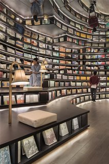 In Hangzhou, China, Shanghai-based XL-Muse designed the Zhongshuge bookstore with forest-like rows of vertical, circular bookshelves and ceilings covered with mirrors. The mirrors make the shelves look much taller than they really are and give the reading hall a dream-like, Dali-esque quality.
