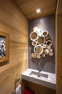 Nature is present throughout the interiors of this French Alpine home, including in the bathroom, where the cross section of tree trunks serve as frames in a cluster of small mirrors.
