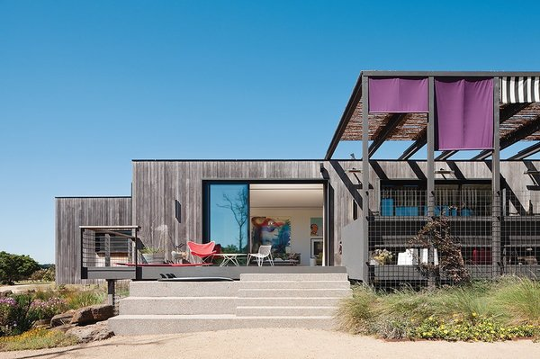 Sitting on the edge of a lake in the Mornington Peninsula, this house by Melbourne-based MA Architects was designed as a series of teak-clad modules with the main living areas in the center and a large deck that extends from the living room.