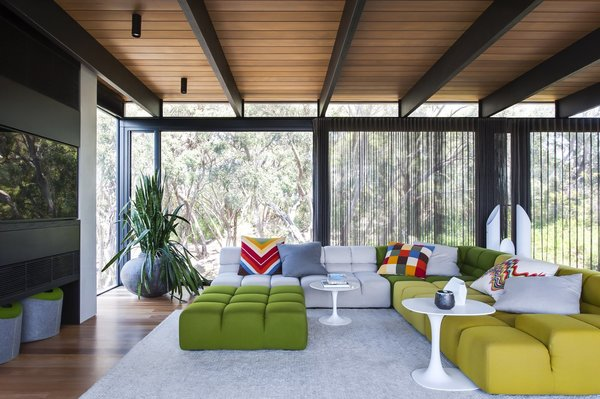 This house in the Mornington Peninsula in the south of Melbourne is filled with materials like natural stone, steel, and cedar, which serve as perfect backdrops for the bold colors and edgy midcentury furniture that firm SJB employed in the space.