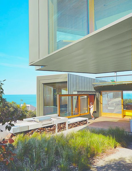 Sited along the Great Ocean Road, this contemporary home in the village of Fairhaven was designed by architect John Wardle. Surrounded by Eucalyptus trees and facing the sea, the house's kitchen leads to an outdoor deck and BBQ area that's perfect for post-surf dinners.