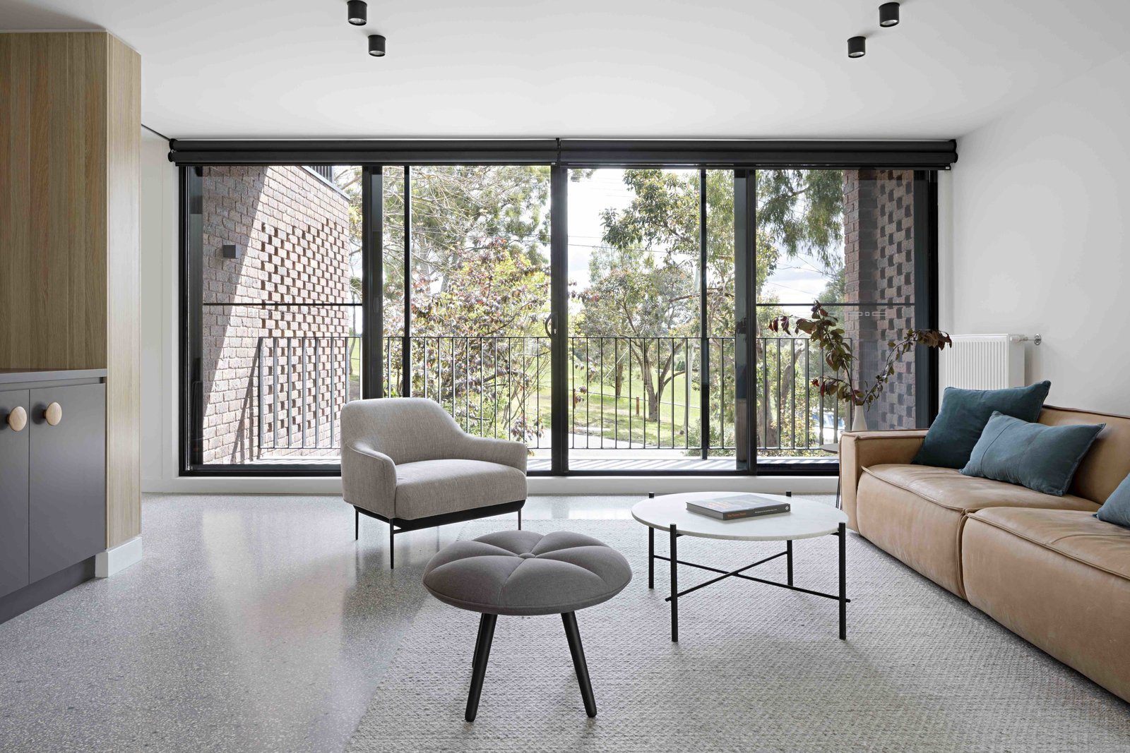 Living Room, Sofa, Coffee Tables, Chair, Ottomans, Rug Floor, and Ceiling Lighting  Photo 10 of 17 in A Remodel Turns a Dark and Choppy House in Melbourne Into a Bright, Flexible Family Home