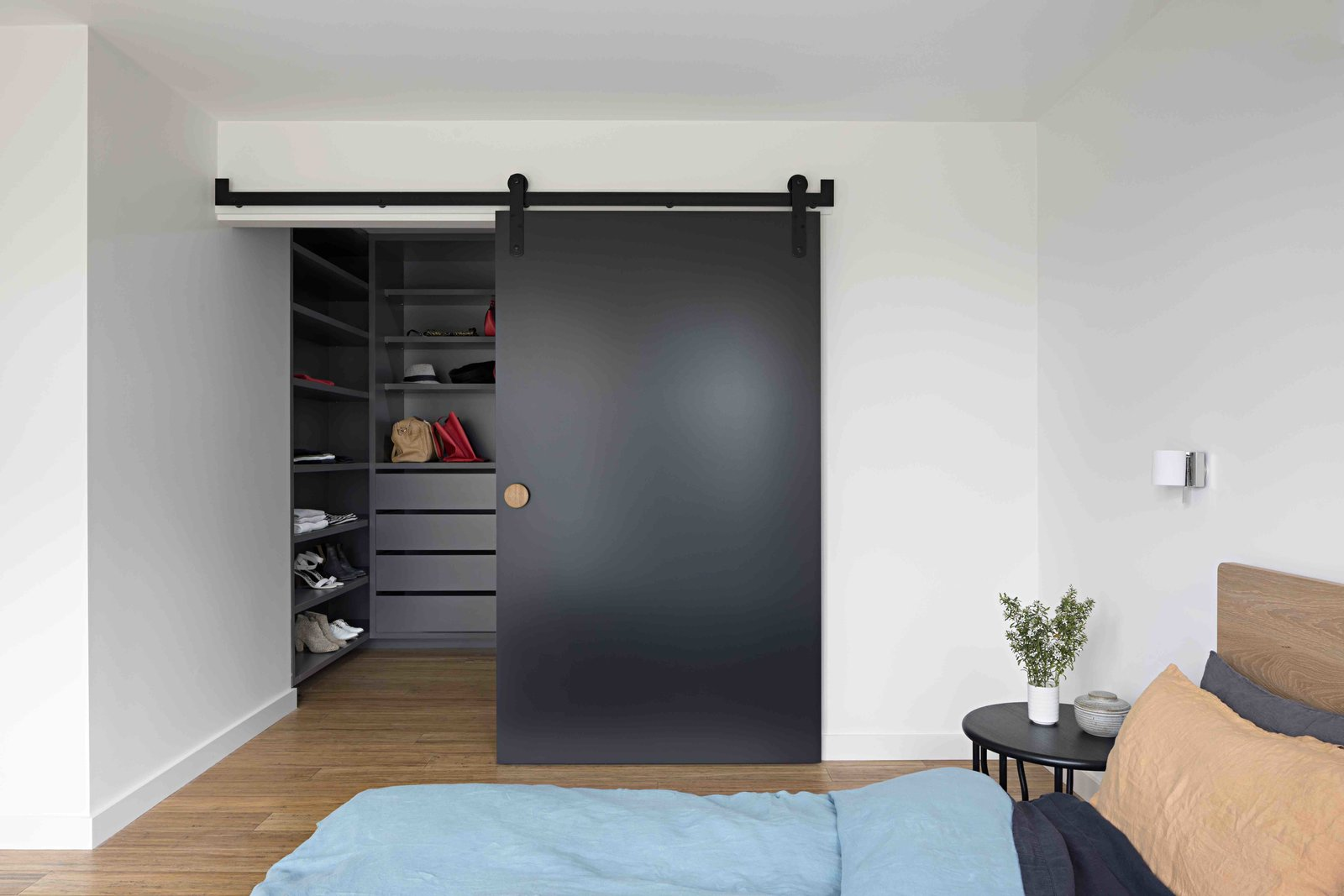 Bedroom, Night Stands, Storage, Shelves, Wall Lighting, and Medium Hardwood Floor  Photo 15 of 17 in A Remodel Turns a Dark and Choppy House in Melbourne Into a Bright, Flexible Family Home