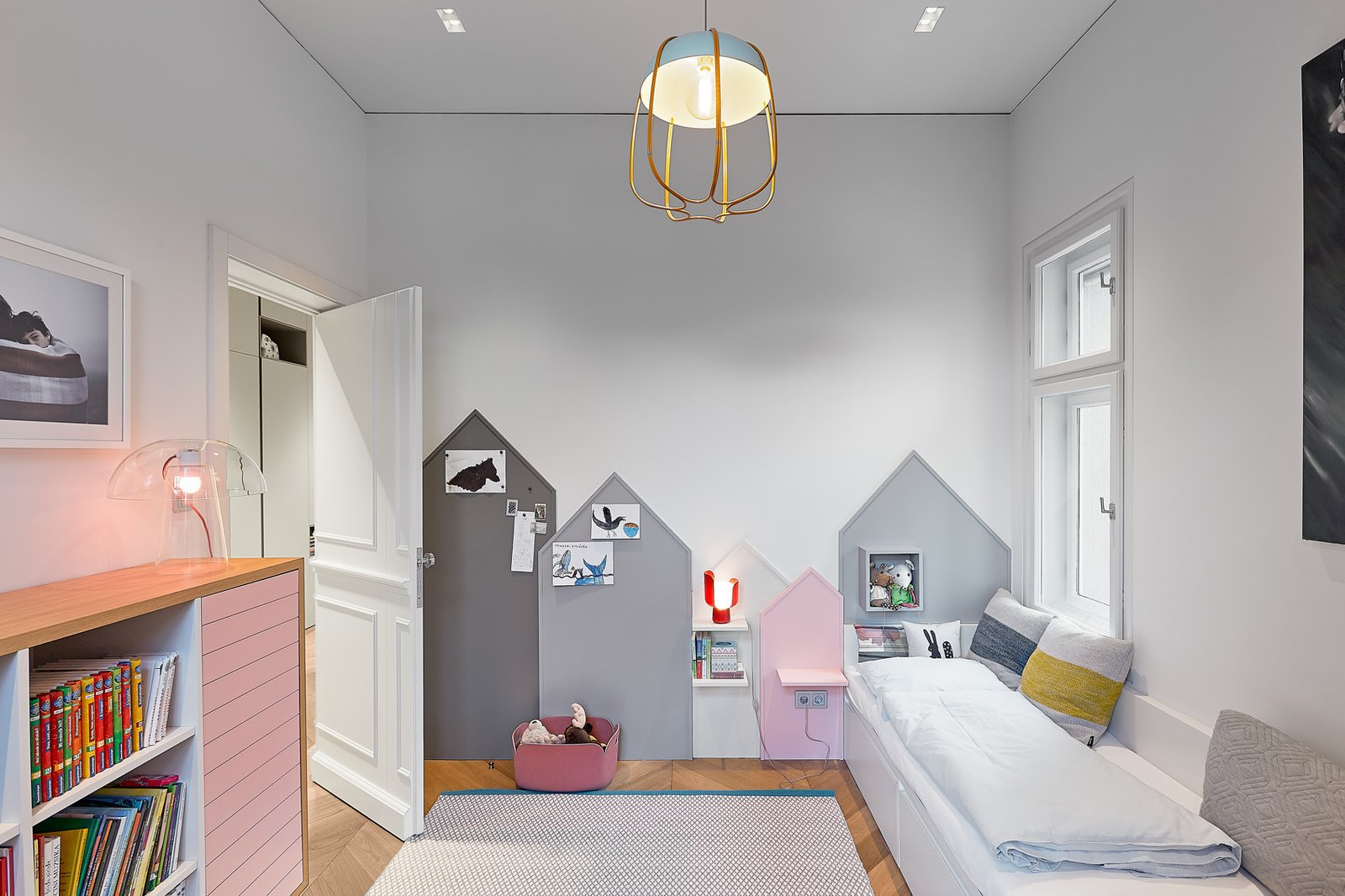 Kids Room, Playroom Room Type, Bedroom Room Type, Storage, Shelves, Lamps, Light Hardwood Floor, and Rug Floor  Photo 10 of 17 in A Family Villa in Budapest With Colorful, 1960s-Inspired Interiors