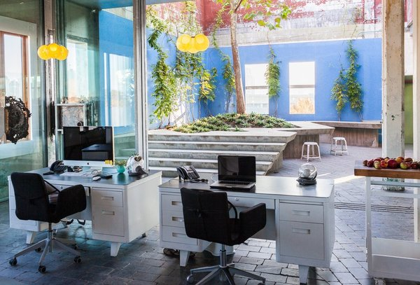 Sculptural lighting and design company Bocci has a bright, outdoor courtyard garden not to far from works stations, where coworkers can take a break and enjoy a little sunshine.  Photo 7 of 9 in 8 Modern Offices That Feel Like Homes