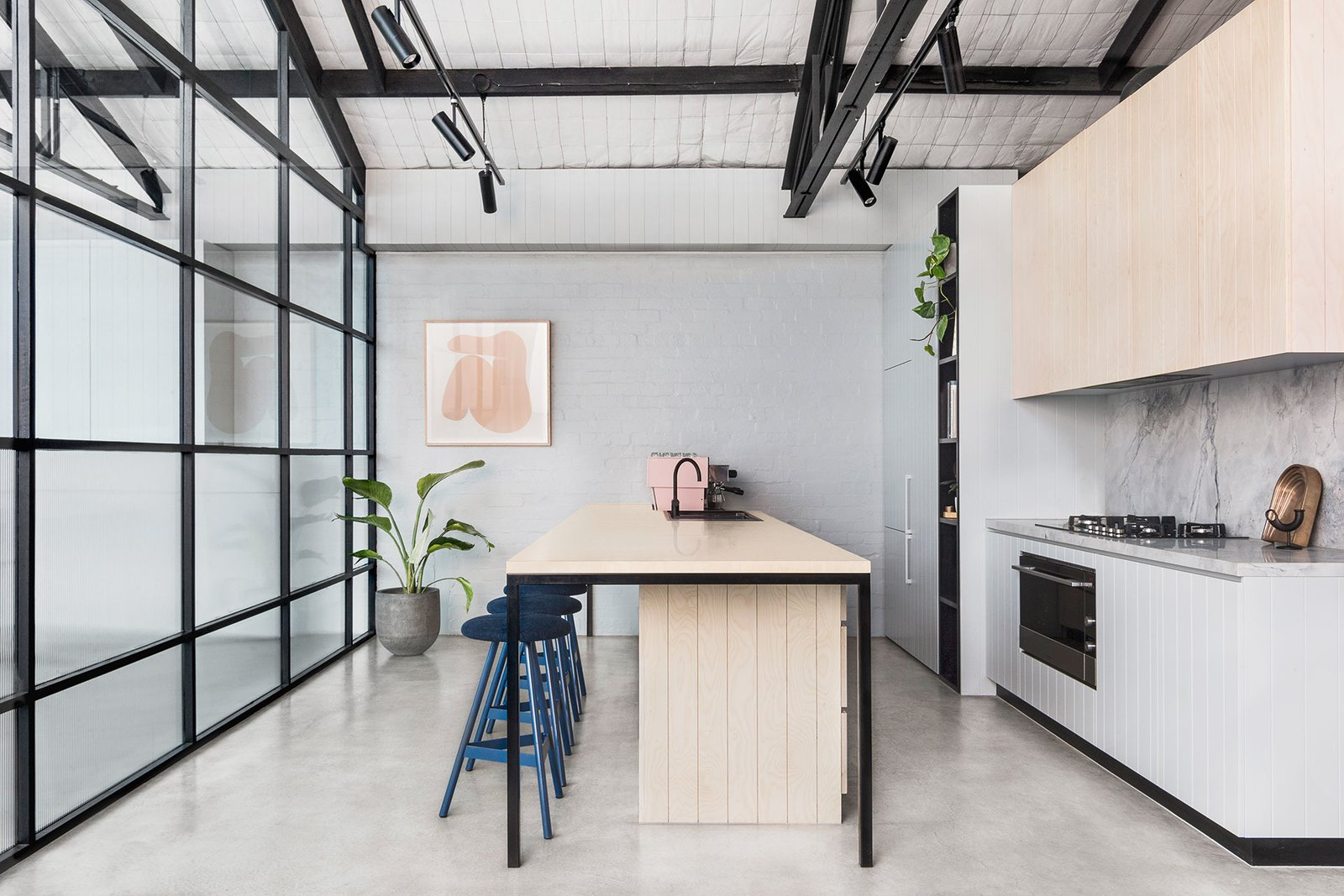Kitchen, Marble Counter, Wood Cabinet, Concrete Floor, Track Lighting, Wall Oven, Range, Drop In Sink, and Marble Backsplashe  Photo 12 of 14 in An Art Deco Warehouse in Melbourne Is Converted Into a Shared Office Space